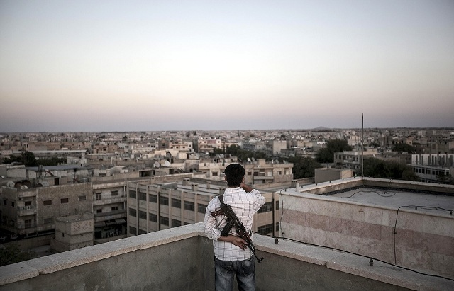 September 13, 2012 - Manbij, Aleppo, Syria: A Free Syrian Army fighter stands guard on the roof of a building as the sun sets over Manbij, a city located at the northeast of Aleppo province. Manbij is the first larger city in Syria to be liberated. Since regime forces withdrew in mid-July, local councils have governed the 150,000 residents of Manbij and the surrounding district, which is home to more than half a million people. After four decades of dictatorship, its residents are suddenly faced with the task of running an independent city-state, one in which neither pensions nor survival can be taken for granted. (Narciso Contreras/Polaris) ///